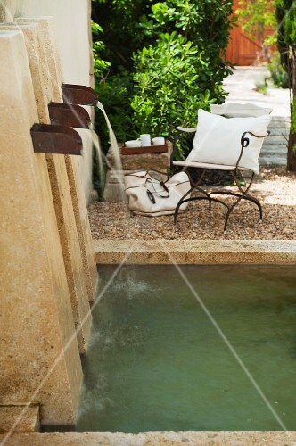 Natural stein water feature with three spouts in a Mediterranean garden; patio chairs on gravel in the background