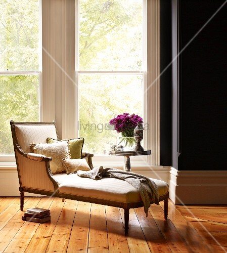 Inviting reading area in front of French windows with scatter cushions on antique chaise longue and side table