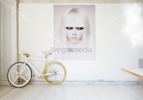 Bicycle below modern portrait of woman on wall in white artist's apartment