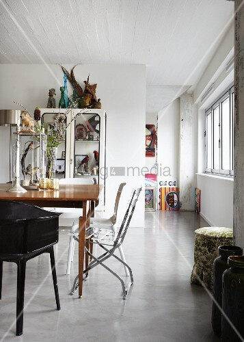Table with various chairs in front of retro display cabinet in loft-style interior