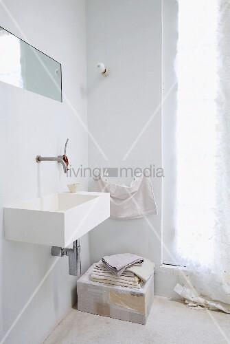eckiges waschbecken mit wandarmatur und in die wand integrierter spiegel im ungefliesten. Black Bedroom Furniture Sets. Home Design Ideas