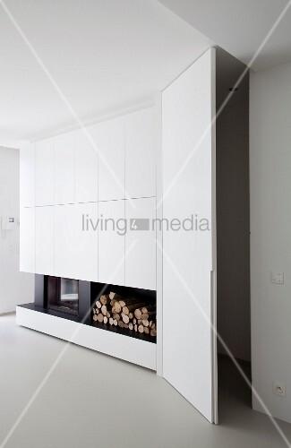 Stauraum mit offener Tür neben weißem Einbauschrank und integriertem Kamin mit Holzlager