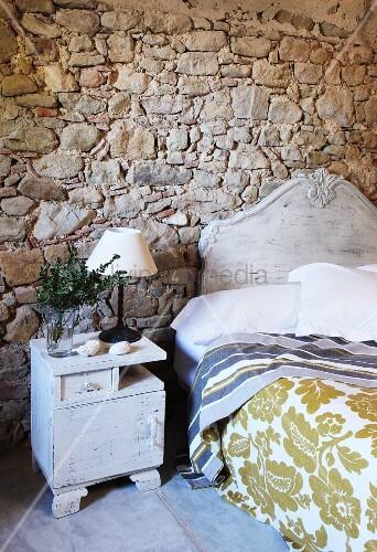 weiss lackiertes vintage bett und nachtkasten vor rustikaler natursteinwand bild kaufen. Black Bedroom Furniture Sets. Home Design Ideas