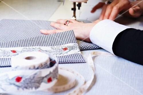 Frau beim Aufnähen eines dekorativen Stoffbandes auf karierten Baumwollstoff