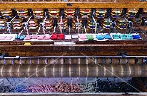 Blick auf alten Jacquard- Webstuhl mit herausrollenden, fertigen Stoffbändern