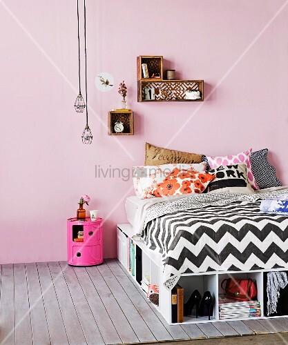 Bett mit vielen Stauraumlösungen, kleine Dekoregale an der Wand und Industrieleuchten über Nachttischbox in fröhlichem Pink