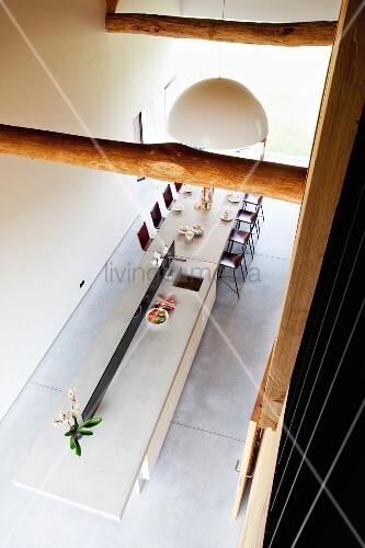 Blick von oben auf lange Esstheke mit Arbeitsfläche und integrierter Spüle im Designerstil