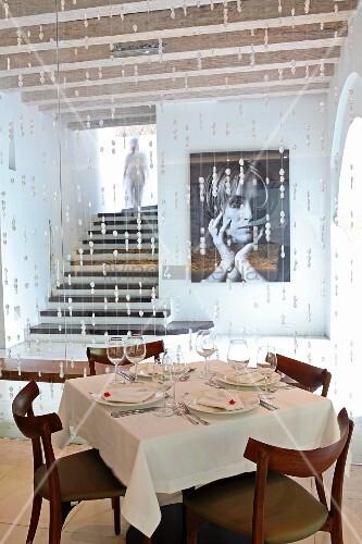 Gedeckter Tisch im Hotelrestaurant vor Perlenvorhang und Blick auf Foto an Wand neben eingeschobenem Treppenaufgang