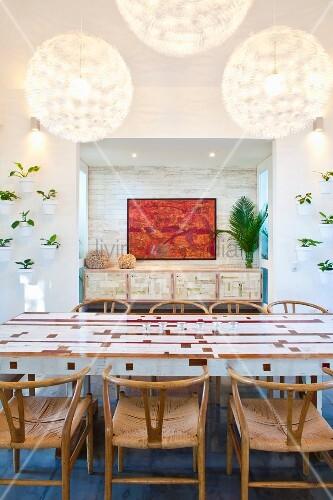 Weisser Esstisch mit Holzintarsien und 50er Jahre Stuhlklassiker; Nische mit Gemälde im Hintergrund