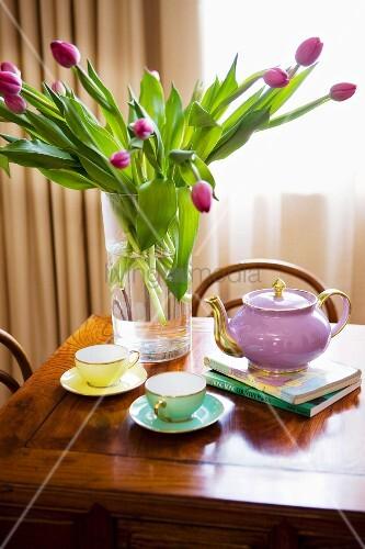Violetter Tulpenstrauss in Glasvase und Teeservice mit Goldrand auf antikem Holztisch