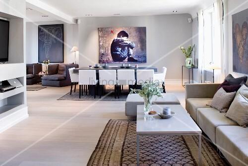 moderne loungeecke vor essplatz mit weissen gepolsterten st hle und grossformatiges bild an. Black Bedroom Furniture Sets. Home Design Ideas