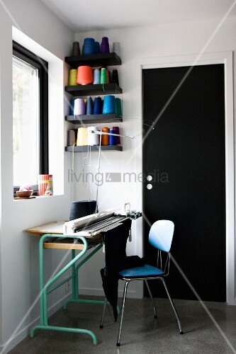 Work area - knitting machine on table with 50s-style chair next to wall-mounted shelves holding spools of brightly coloured yarn