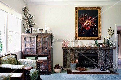 polstersessel neben schrank im kolonialstil und rustikale kaminst tte unter gerahmtem bild im. Black Bedroom Furniture Sets. Home Design Ideas