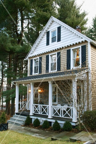American wooden house with a porch in front of tall trees at dusk
