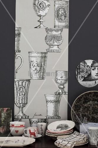 Geschirr auf Tisch vor läuferartigem Streifen an schwarzer Wand mit Pokalmotiven