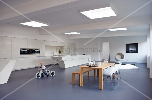 Child on tricycle in minimalist interior with dining area and futuristic counter