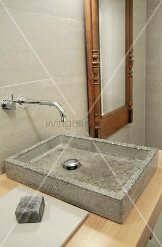 waschbecken aus beton auf holzplatte und designer wandarmatur neben spiegel mit antikem. Black Bedroom Furniture Sets. Home Design Ideas