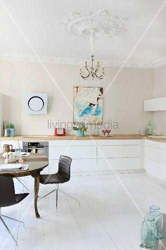anitker esstisch und moderne st hle in renovierter k che mit stuckarbeiten an wand und decke. Black Bedroom Furniture Sets. Home Design Ideas