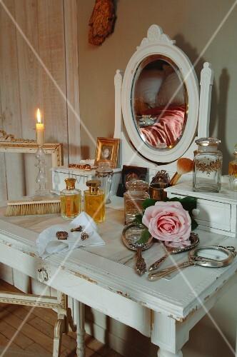 Antiker Schminktisch im Shabbylook mit versilberten Handspiegeln, Parfumflaschen und Rosenblüte