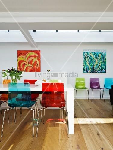 farbige kunststoff st hle an weissem esstisch gegen ber wand mit modernen bildern bild kaufen. Black Bedroom Furniture Sets. Home Design Ideas