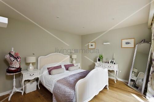 Traditionelles Schlittenbett gegenüber Standspiegel in hell getöntem Schlafzimmer