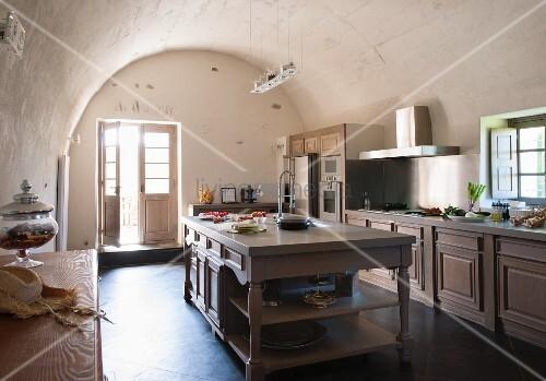 Traditionelle, schlichte Küche mit Mittelblock unter Tonnendecke in mediterranem Landhaus