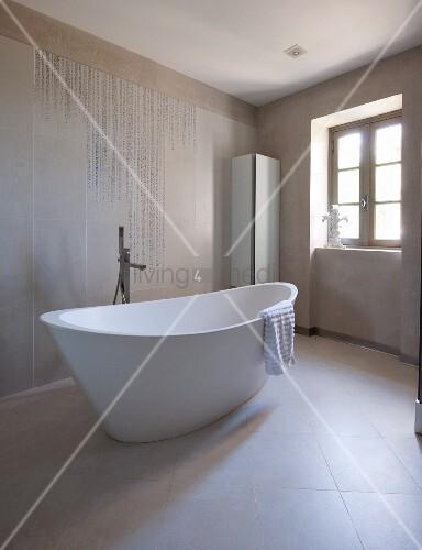 Freistehende Designer  Badewanne Und Standarmatur In Modernem Bad Mit  Hellen Fliesen An Wand Und Boden