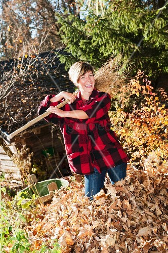 Woman standing in heap of autumn leaves with besom broom on shoulder