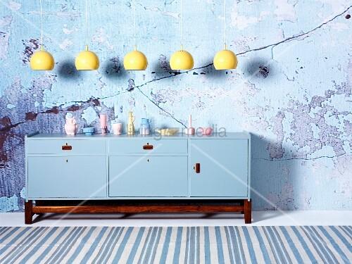 gelbe h ngeleuchten in reihe ber hellblau lackiertem sideboard auf holz sockelgestell vor wand. Black Bedroom Furniture Sets. Home Design Ideas