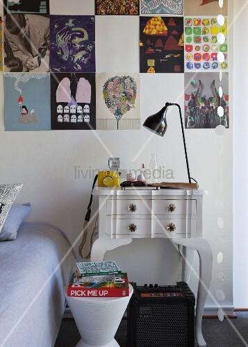 Ausschnitt eines Schlafzimmers mit modernem Hocker vor Vintage Nachttisch an Wand mit gepinnten Postern