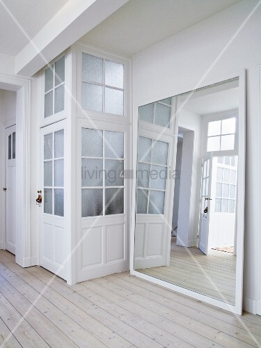 Large Framed Mirror Leaning Against Wall Next To Doors With Latticed Gl Panels In Foyer