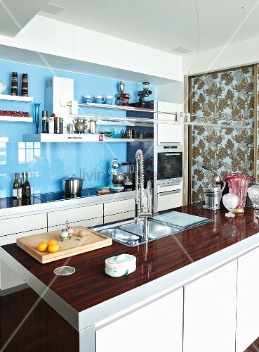 Modern kitchen with glossy splashback and white cupboard doors; sliding door with pattern of autumnal leaves in background