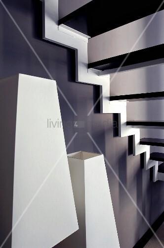 Weisse Lampenschirme unter Treppenlauf vor schwarz getönter Wand