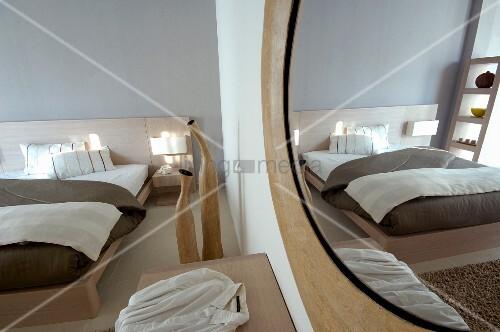 Modernes Doppelbett mit hellem Holzgestell und rundem Wandspiegel gegenüber