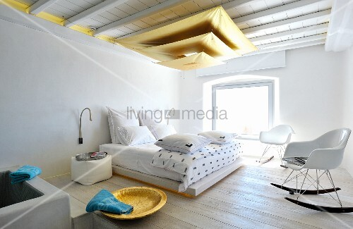 Pendant lamp made from three suspended gold sails in Mediterranean bedroom with Bauhaus rocking chair in front of double bed