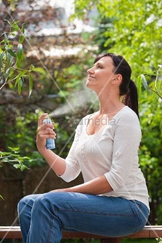 Woman misting her face with water