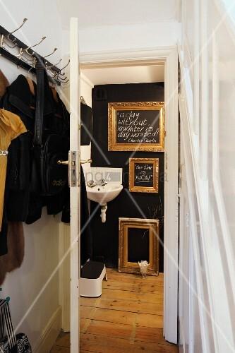 Wandgarderobe im Vorraum und Blick durch offene Tür auf schwarze Wand mit goldenen Bilderrahmen und Eckwaschbecken