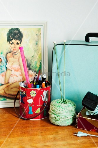 Picture of woman, bag, metal can of pens & knitting yarn on cabinet