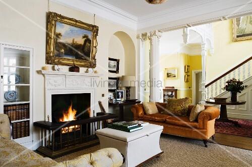 Verschiedene, traditionelle Polstermöbel vor brennendem Kaminfeuer in englischem Herrenhaus