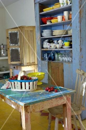 vintage k che erdbeeren im korb auf esstisch mit abbl tternder farbe vor rustikalem. Black Bedroom Furniture Sets. Home Design Ideas