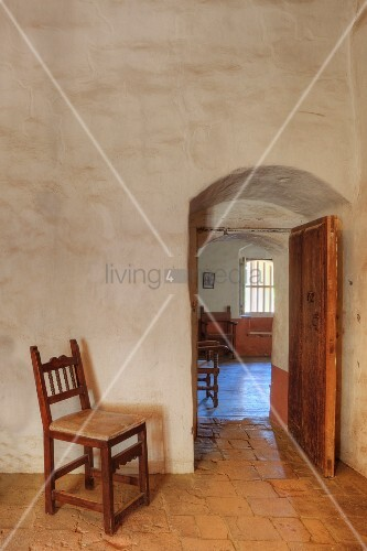 Empty chair gaurds interior doorway of adobe building, Mission La Purisima State Historic Park, Lompoc, California
