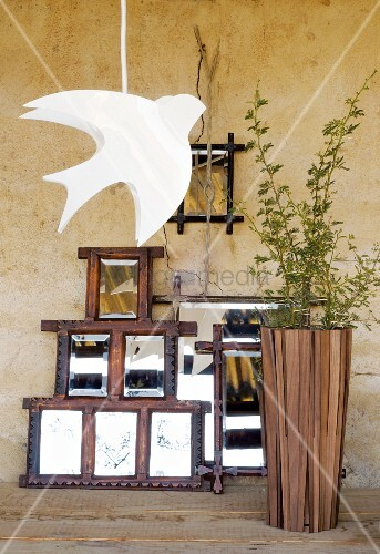 Collection of original mirrors leaning on rustic wall; white bird-shaped pendant lamp and tall wooden floor vase in foreground