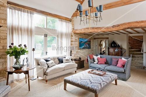 Elegantes Wohnzimmer mit rustikalen Steinwänden und Holzbalken; in der Raummitte zwei Sofas im Vintage-Stil und ein quadratischer Polstertisch