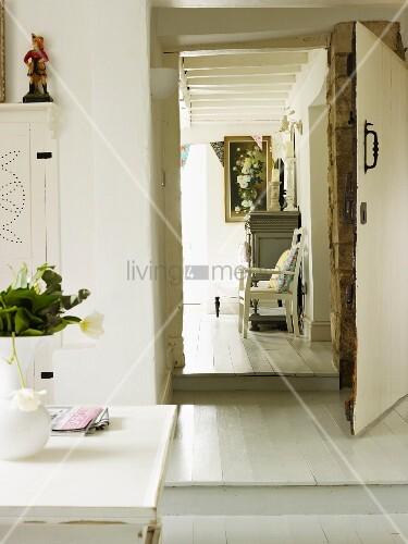 Blick aus einer hellen Wohnküche durch eine Tür in das Wohnzimmer