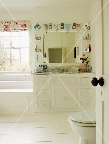 Helles Badezimmer mit weissen Möbeln, Wandspiegel mit Wimpelkette und weißem Holzboden