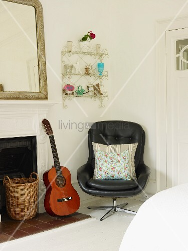 Zimmerecke mit Drehstuhl, Gitarre, Wandregal und offenem Kamin