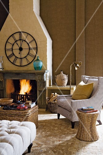 Rattan stool next to armchair and coffee table in front of fire in open fireplace below traditional, wrought iron wall clock