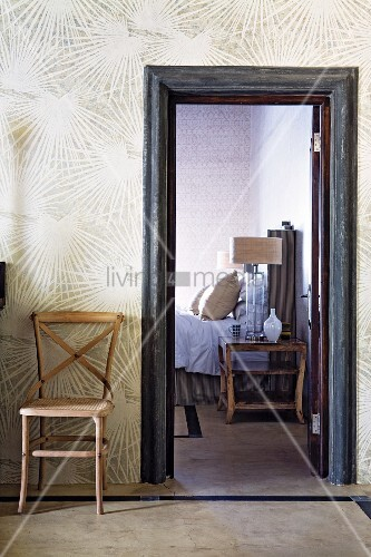 Simple wooden chair against wallpaper with sunburst pattern next to open door leading to bedroom