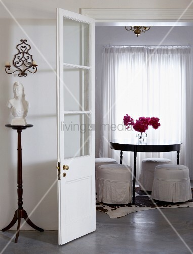 View into white dining room with round table, upholstered stools with white, loose covers; bouquet of bougainvillea on table