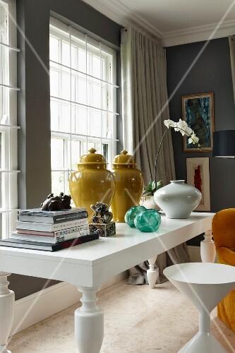 Chinesische Vasen neben Bücherstapel und weissen Orchideen auf weißem Tisch mit weißem Hocker